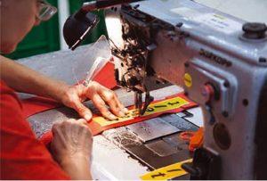 Un'addetta di Sabelt al lavoro per cucire le cinture destinate anche alla Formula 1